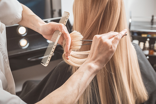 An image of a woman getting her hair cut